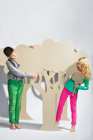 tryst: Love concept. Couple of kids. boy and girl hiding behind a cardboard tree. Stock Photo