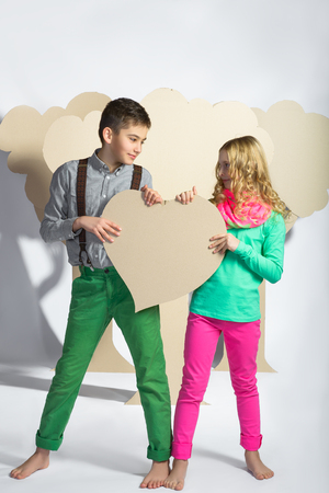 tryst: Love concept. Couple of kids. Boy and girl holding a cardboard heart.