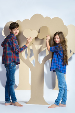 ragazza innamorata: Ragazzo con la ragazza nasconde dietro l'albero di cartone e in possesso di un cuore di cartone. Concetto di amore. Archivio Fotografico