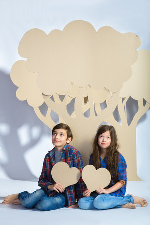 tryst: boy and girl keep hearts and sit under cardboard tree. Love concept.