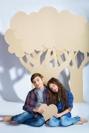 ragazza innamorata: ragazzo e ragazza tenere i cuori e si siedono sotto l'albero di cartone. Concetto di amore. Archivio Fotografico