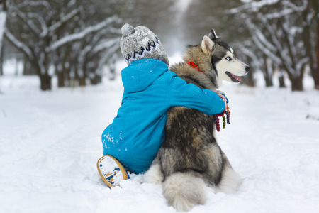 happy boy hugging dog or husky outdoors in winter day.