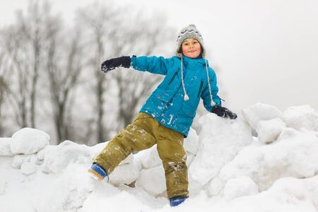 cute boys: Happy baby boy playing snow in winter day.