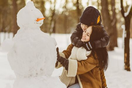 Happy family in warm clothing. Smiling mother and son making a snowman outdoor. The concept of winter activities.