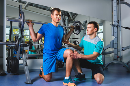 Personal trainer helping a young man doing squats with a heavy barbell