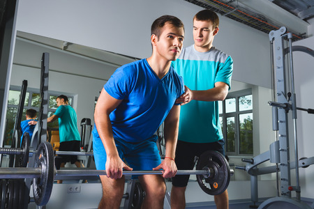 Muscular Man Lifting Deadlift In The Gym with instructor.