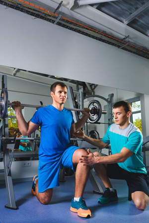 squats: Personal trainer helping a young man doing squats with a heavy barbell