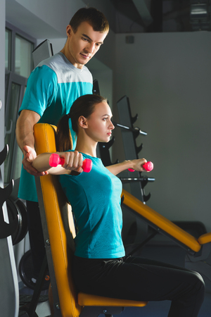 deltoid: Young woman doing shoulders workout with dumbbells in a gym.