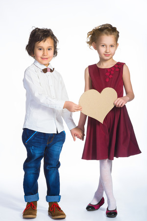 tryst: Boy and girl holding a cardboard heart. Love concept. Stock Photo