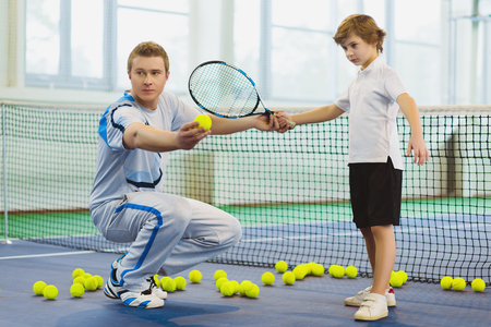 male tennis players: Instructor or coach teaching child how to play tennis on a court indoor.
