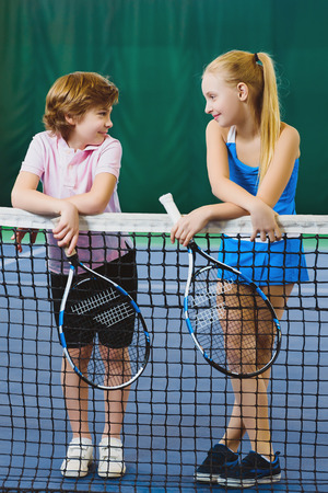 Cute girl and boy or children playing tennis and posing in court indoor. Zdjęcie Seryjne