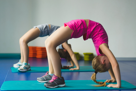 Girls doing gymnastic exercises or exercising in fitness class. Zdjęcie Seryjne