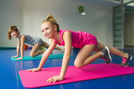 Girls doing gymnastic exercises or exercising in fitness class. Stock Photo