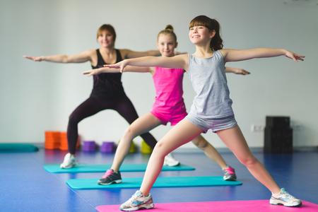 Ragazze e Istruttore o madre che esercitano ginnastica in classe fitness.