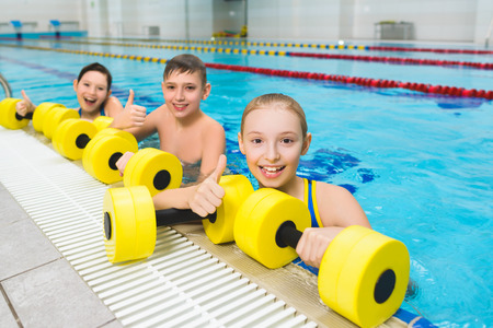 Happy and smiling group of children doing exercises in a swimming pool.