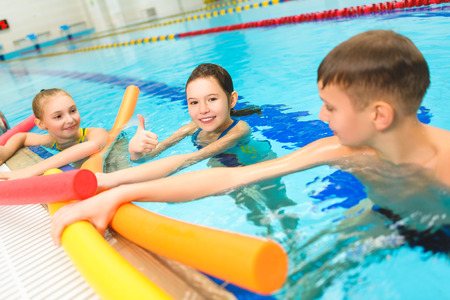 Happy and smiling group of children learning to swim with pool noodle. Zdjęcie Seryjne