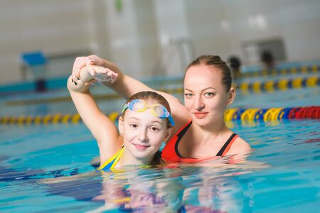teaches: instructor teaches the girl swimming in a pool.