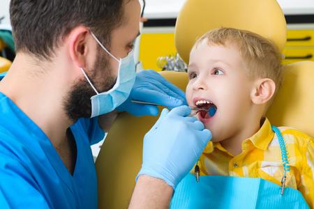 examined: Close up of boy having his teeth examined by a dentist.