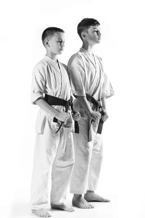 karate boy: Karate boy in kimono fighting on a white background. Stock Photo