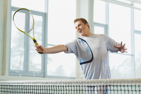 innings: Low angle view of determined young man playing tennis indoor. Stock Photo