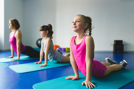 yoga class: Girls and Instructor or mother doing gymnastic exercises  in fitness class.