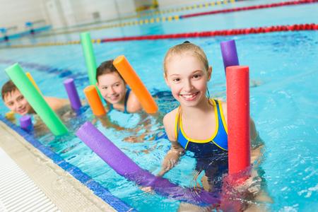 Gelukkig en lachende groep kinderen leren zwemmen met zwembad noodle.
