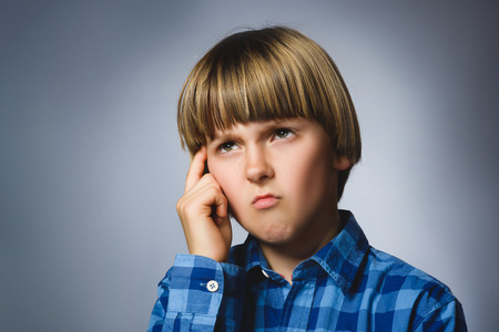 musing: Close up Thoughtful Young Boy Looking Up with Hand on the Face Against Gray Background with Copy Space.