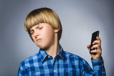 exasperation: Closeup Portrait of worried stressed boy with mobile going irritation on gray background.