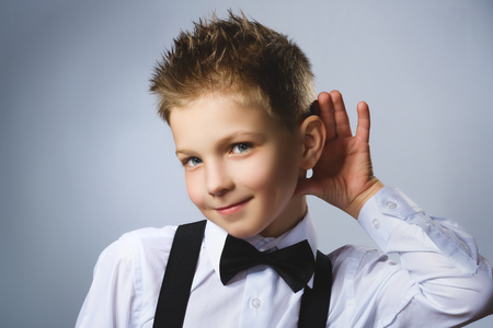 talk to the hand: Curious Disappointed boy listens. Closeup portrait child hearing something, parents talk, hand to ear gesture isolated grey background. Human face expression, emotion, body language, life perception.