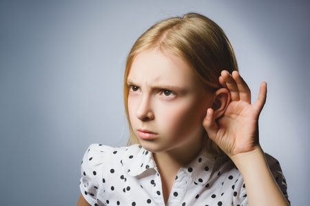 talk to the hand: Curious Disappointed girl listens. Closeup portrait child hearing something, parents talk, hand to ear gesture isolated grey background.