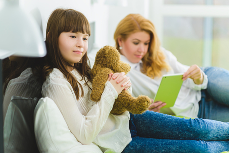 fond of children: happy family. joyful and dreaming daughter holding teddy bear lies beside mom.