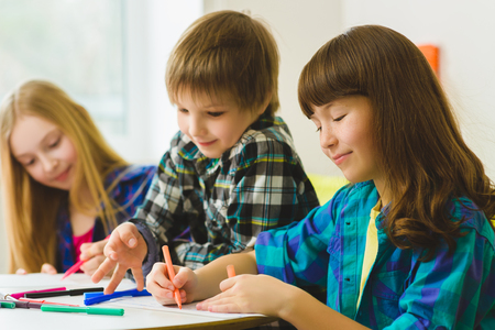 drawing room: happy Little girls and boy drawing pictures. Indoor at room.