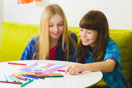 drawing room: happy Little girls drawing pictures. Indoor at room.