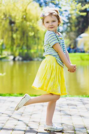 little girl posing: cute stylish little girl posing at park.