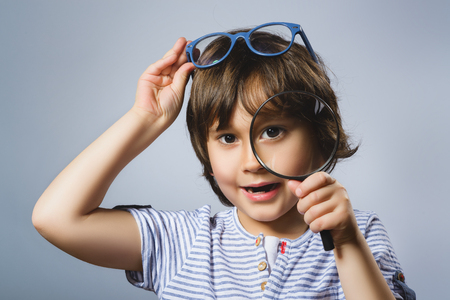 see through: Child See Through Magnifying Glass, Kid Eye Looking with Magnifier Lens over Gray. Stock Photo