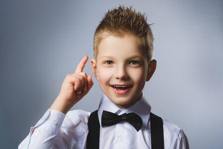 resourceful: Closeup Portrait of gestured child  on grey background. Boy found the idea or solution.