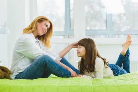 contented: happy family. joyful contented mother stroking her daughters hair. Stock Photo