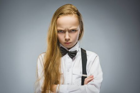 delito: Retrato de niña delito aislado sobre fondo gris. las emociones humanas negativas, la expresión facial. De cerca.