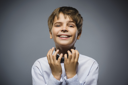 supplicate: Happy boy. Closeup Portrait of handsome teen in casual shirt smiling while standing against grey background.