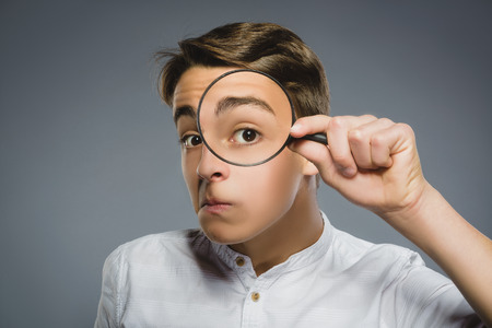 see through: Boy See Through Magnifying Glass, Kid Eye Looking with Magnifier Lens over Gray. Stock Photo