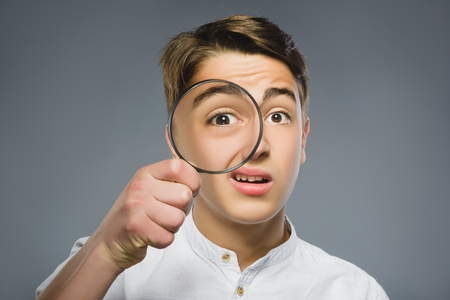 Boy See Through Magnifying Glass, Kid Eye Looking with Magnifier Lens over Gray. Stock Photo