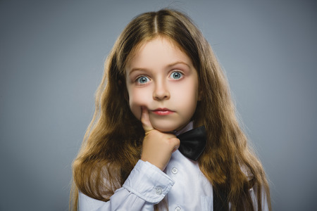 introspective: Closeup Thoughtful Young girl Looking Up with Hand on Face isolated on Gray Background. Stock Photo