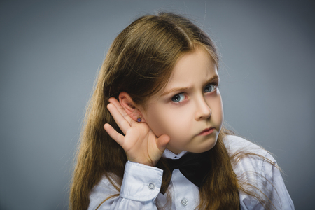 talk to the hand: Curious Disappointed girl listens. Closeup portrait child hearing something, parents talk, hand to ear gesture isolated grey background. Human face expression, emotion, body language, life perception. Stock Photo