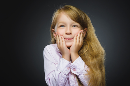 manic: Closeup Portrait of happy girl going surprise isolated on gray background. Stock Photo