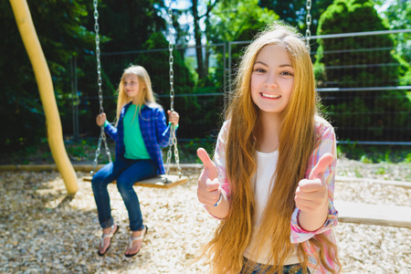 Portrait of happy and smiling child show thumb up at park. On the background other girl riding a swing. Stock Photo