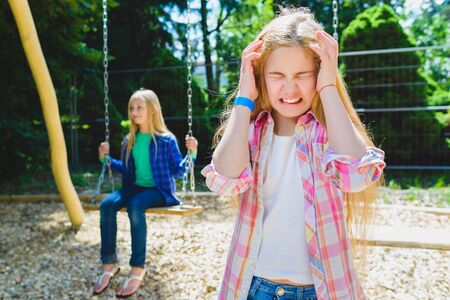 delito: Retrato de ni�o en el parque de delito. En el fondo de otra chica de montar un columpio. Foto de archivo