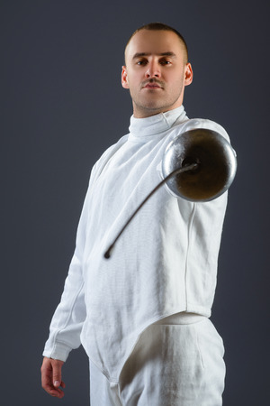 Fencing athlete posing with a sword or epee on gray background. Stock Photo