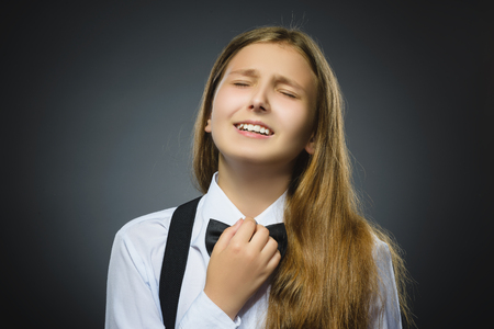 misconduct: Portrait of offense girl isolated on gray background. Negative human emotion, facial expression. Closeup. Stock Photo