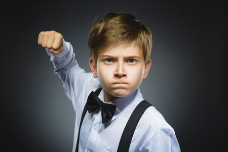 Portrait of angry boy isolated on gray background. He raised his fist to strike. Stock Photo