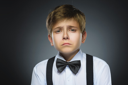 Portrait of offense crying boy isolated on gray background. Negative human emotion, facial expression. Closeup. Stock Photo